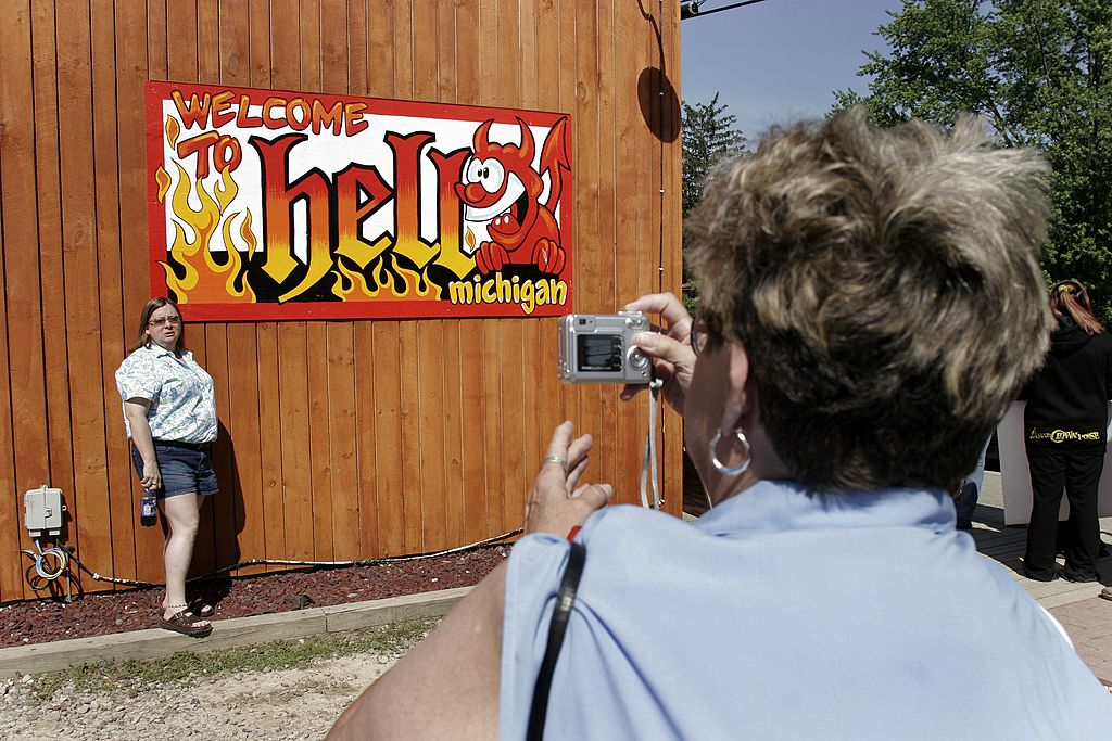 FILE - A woman poses for a picture under a sign outside Screams Ice Cream shop to mark the date 666 (an abbreviation of  6/6/06) June 6, 2006 in Hell, Michigan.