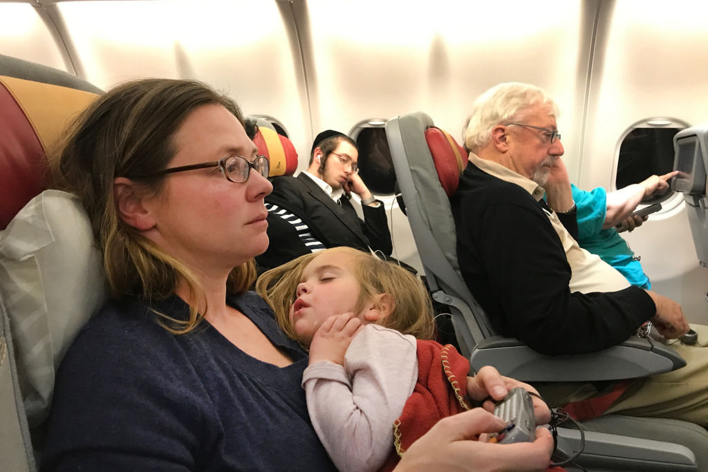 FILE:  A mother with her sleeping three year old daughter on a flight from New York to Rome. Italy. 22nd October 2017.
